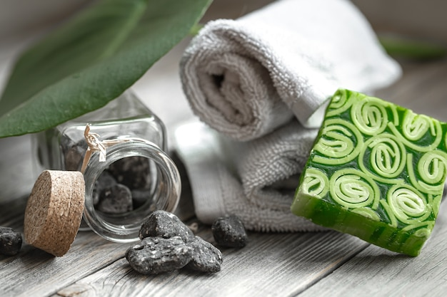 Spa still life with stones in a jar, handmade soap and towels. health and beauty concept.