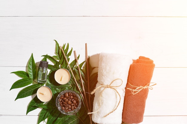 Spa still life with towel candles and green leaves on a white wooden surface sun flare