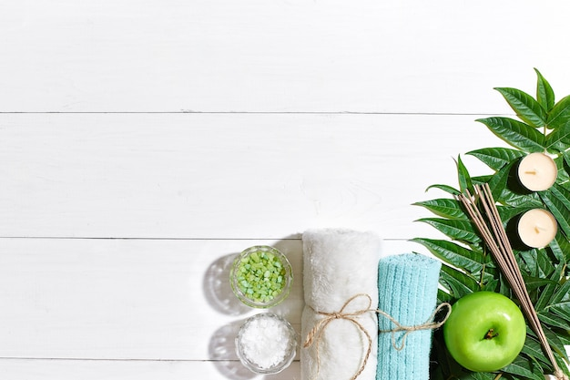 Spa still life with towel candles and green leaves on a white wooden surface