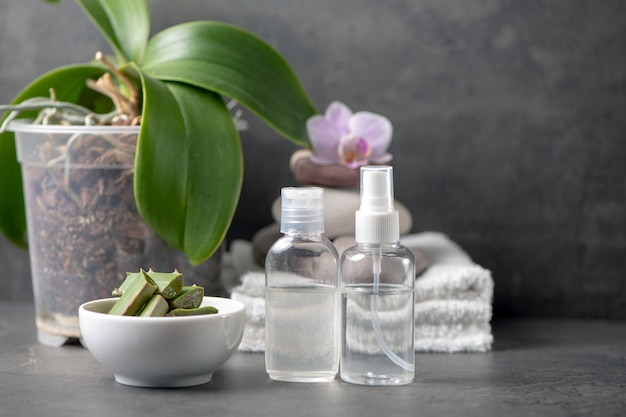 Spa still life with towel and orchid and aloe vera on gray cement background
