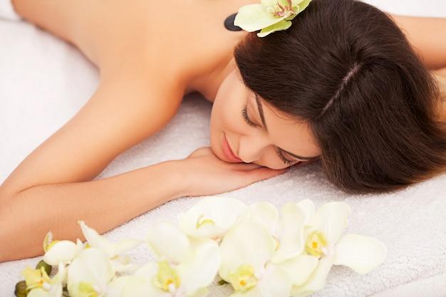 Spa stone massage. beautiful woman getting spa hot stones massage in spa salon. beauty treatments outdoor. nature