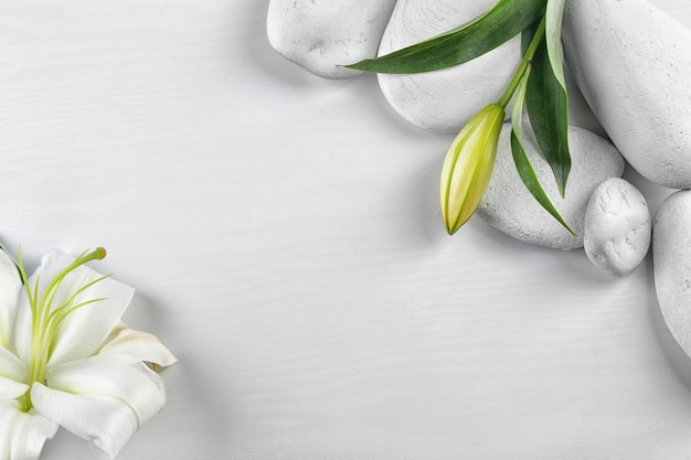 Spa stones and beautiful lily on white wooden table