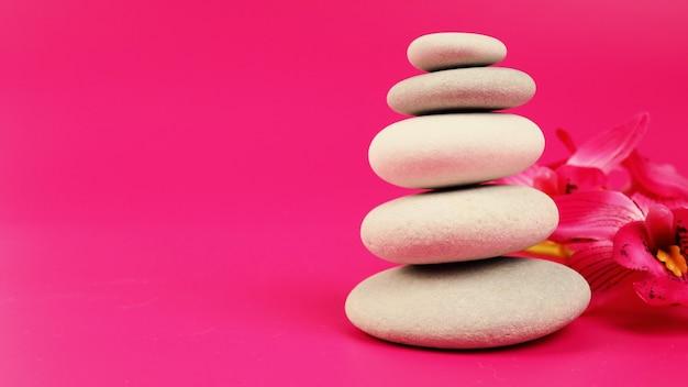 Спа-массаж с камнями, расслабляющая процедура, каменная пирамида на полосатом серо-белом фоне, башня из пяти камней, простые уравновешенные камни, простота, гармония и баланс, рок-дзен