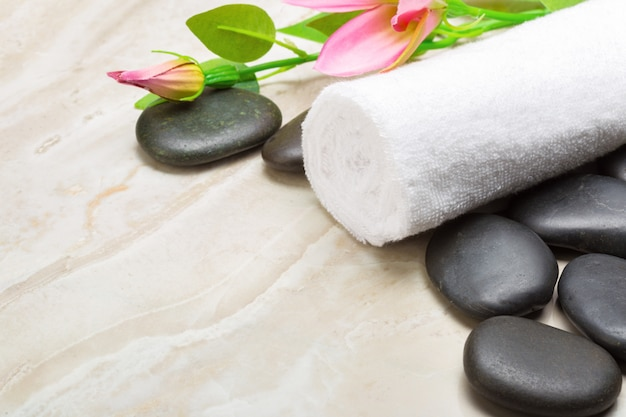 Spa stones, towel and flowers on wooden background
