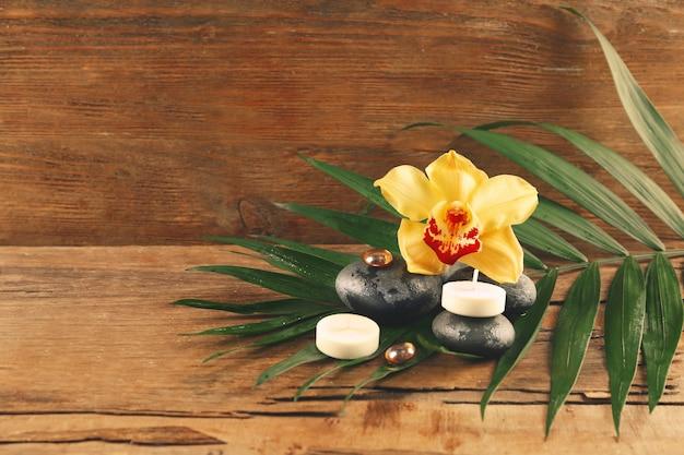 나무 배경에 아름다운 꽃과 촛불이 있는 스파 돌