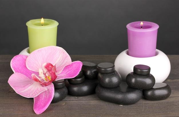 灰色の木製テーブルに蘭の花とキャンドルとスパの石