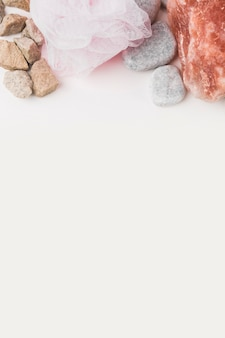 Spa stones with pink loofah on white background with copy space for text