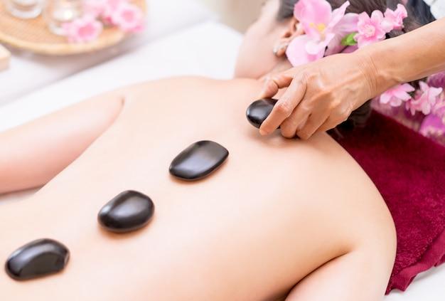 스파 치료사는 여자에게 검은 뜨거운 돌을 씌우고 있습니다.