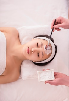 Spa therapy for asian woman receiving facial mask.