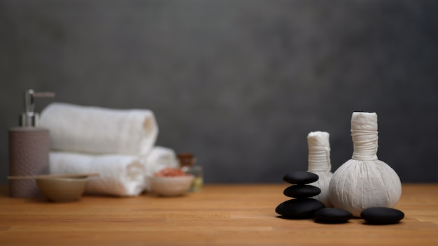 Spa therapy concept: cropped shot of spa table with spa accessories and copy space on wooden table