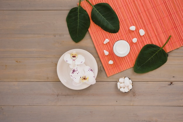 Spa tools with green leaves placed on wooden table