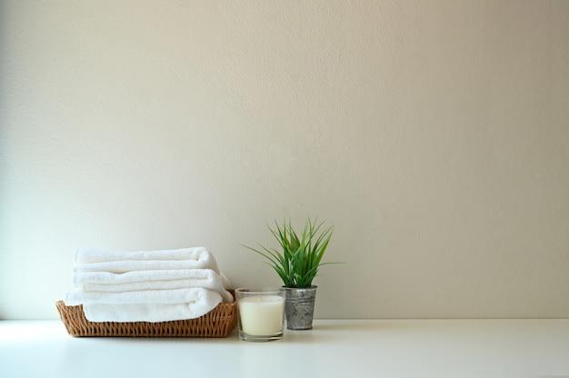Spa towel and candle on bathroom shelf with wall.