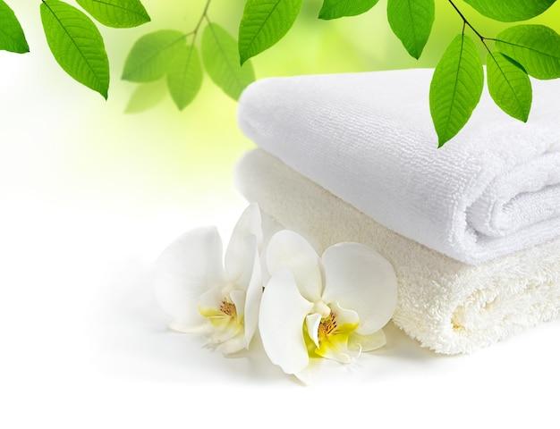 흰 난초 꽃과 흰색 배경에 녹색 잎 스파 수건