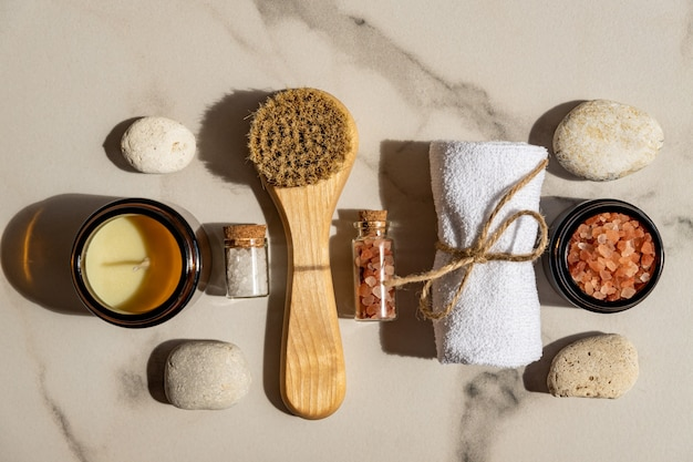 Spa treatment accessories on a marbl table - white cotton towel, face brash, sea salt and aroma candle for relaxing atmospthere.