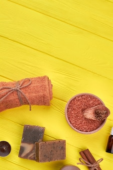 Аксессуары для спа-процедур на желтом деревянном столе. вертикальное свернутое полотенце с солью и мылом.