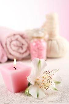 밝은 배경의 나무 테이블에 있는 스파 트리트먼트와 꽃
