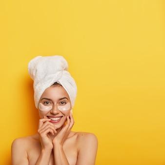 Санаторно-курортное лечение и концепция гигиены. красивая молодая женщина со свежей здоровой кожей, носит косметические патчи под глазами, уменьшает отечность и темные круги