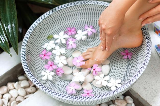 여성 피트 스파 트리트먼트 및 제품. 열 대 꽃, 태국 그릇에 발 목욕. 건강한 개념.