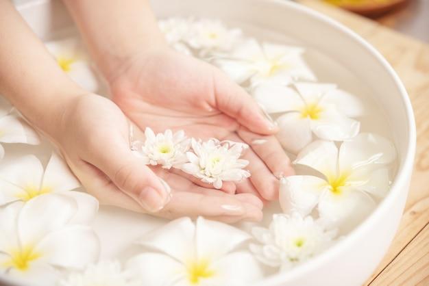 スパトリートメントと製品。スパでのアロマテラピーのための水とセラミックボウルの白い花。