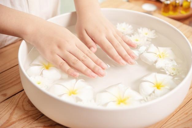스파 트리트먼트 및 제품. 스파에서 아로마 테라피를 위해 물과 세라믹 그릇에 흰 꽃.