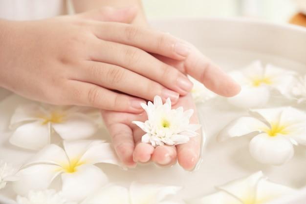 Санаторно-курортное лечение и продукт. белые цветы в керамической миске с водой для ароматерапии в спа.