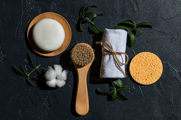 Spa treatment assessories on black background. face massaging brush, cotton towel, natural sponge and handmade organic soap bar with herbal extract
