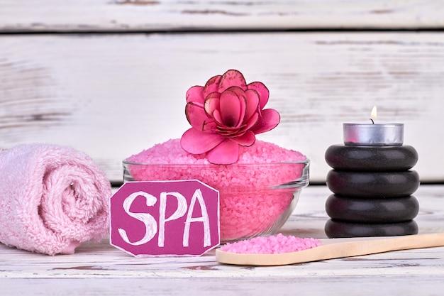 스파 치료 개념입니다. 압연 수건과 돌 핑크 소금입니다.