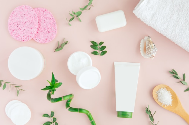 Spa treatment on pink with bamboo stalk and green leaves, flat lay