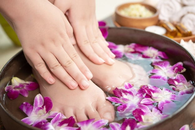 Spa treatment and product for female feet and hand spa. orchid flowers in ceramic bowl.