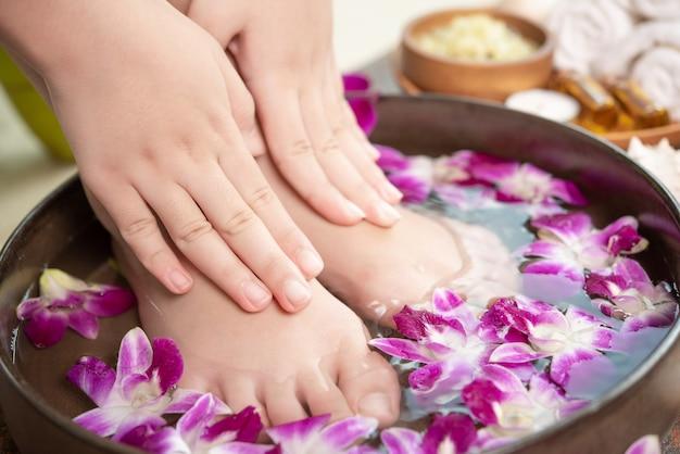 Trattamento termale e prodotto per piedi femminili e spa per le mani. fiori di orchidea in ciotola di ceramica.