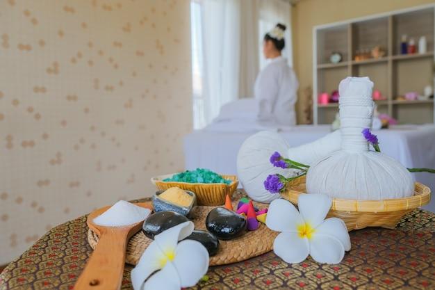 スパトリートメントセットとベッドマッサージのアロママッサージオイル。アロマテラピーとベッドの上の花を使ったマッサージのためのタイの設定、リラックスして健康的なケア。