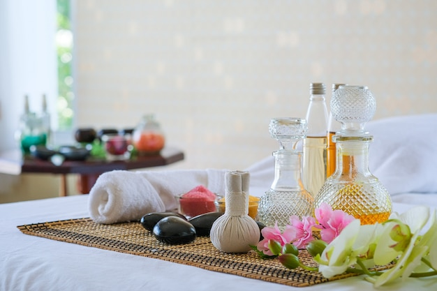 Spa treatment set and aromatic massage oil on bed massage. thai setting for aroma therapy and massage with flower on the bed, relax and healthy care.