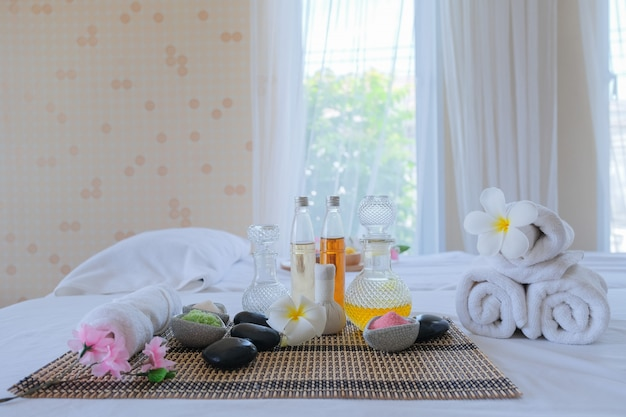 Spa treatment set and aromatic massage oil on bed massage