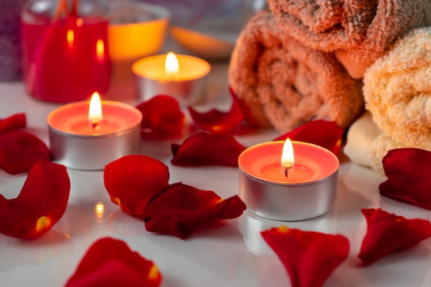 Spa treatment set with scented oil, candles, rose petals and flowers