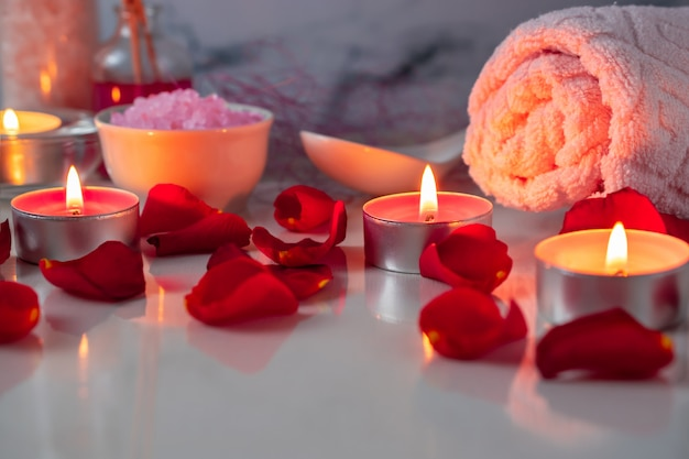 Spa treatment set with scented oil, salt, candles, rose petals and flowers