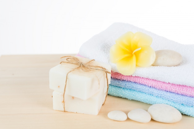 Spa and treatment settting with zen stones, towels, coconut soap and frangipani flowers on wooden table