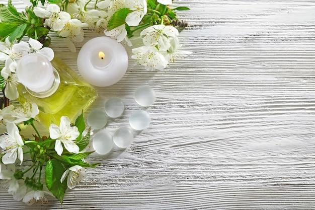 白い木製のテーブルに咲く枝とスパトリートメント