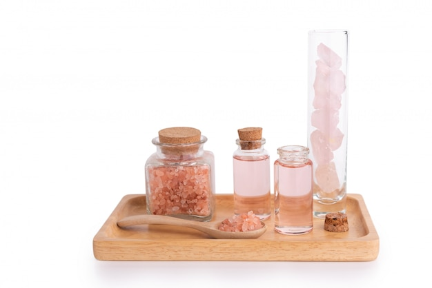 Spa treatment with liquid soap, pink salt and stones on wooden tray isolated on white with path
