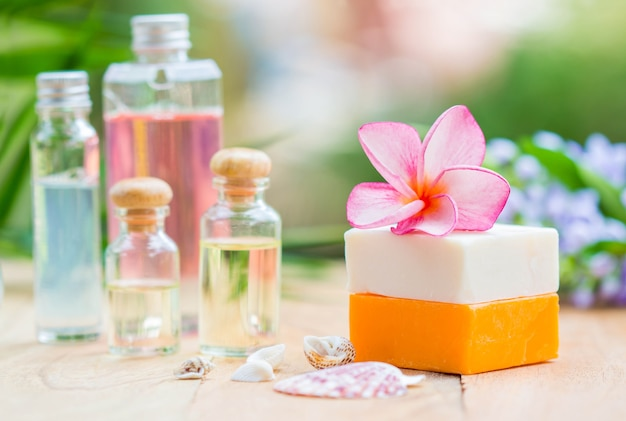 Spa treatment with scented candles and soap on wood.