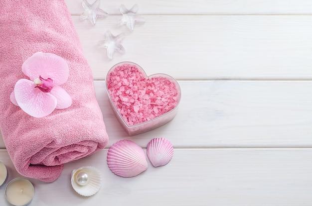 バレンタインデーへのギフトとしてのスパトリートメント。コピースペースと白い木製の背景にハートの形をした花、貝殻、ピンクの海塩とピンクのタオル。ビューティーサロン、マッサージ。-