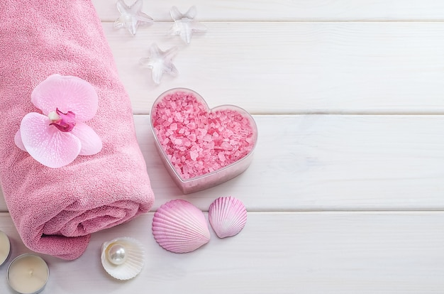 Spa treatments as a gift for valentine's day. pink towel with flower, shells and pink sea salt in the shape of a heart on a white wooden background with copy space. beauty salon, massage.
