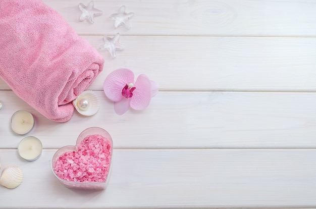 Spa treatments as a gift for valentine's day. pink towel with flower, shells and pink sea salt in the shape of a heart on a white wooden background with copy space. beauty salon, massage.-