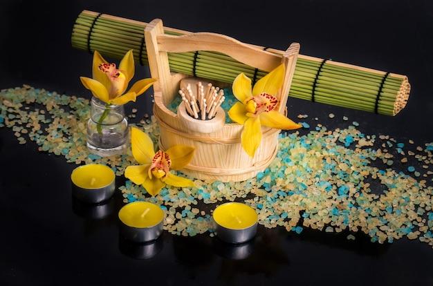 스파 트리트먼트 개념. 난초 꽃, 바다 소금, 양초 및 검정색 배경에 개체.