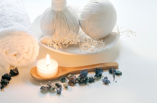 Spa treatments set with herbal compressing ball, candles and towel