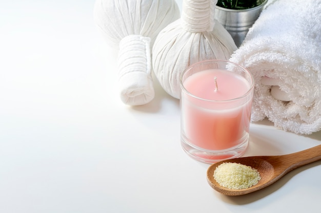 Spa treatments set with spoon of salt, herbal compressing ball, candles and towel