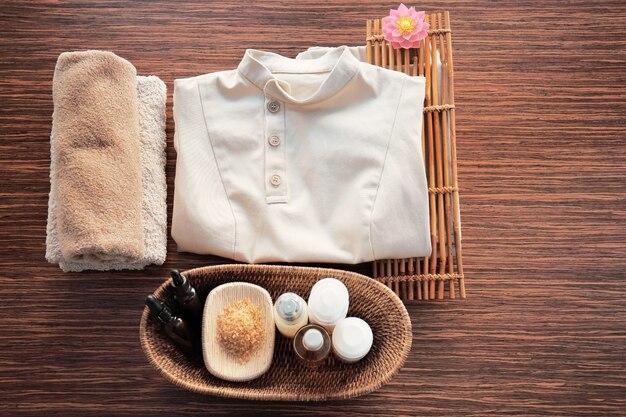 Спа-униформа и принадлежности массажиста на деревянных фоне