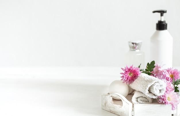 핑크 꽃과 함께 개인 위생 및 미용 제품이있는 스파 벽. 위생 및 바디 케어 개념.