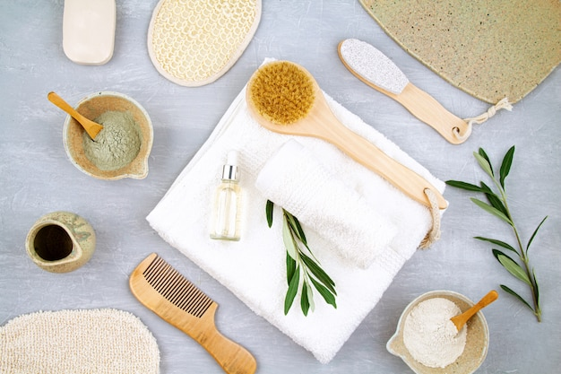Spa and wellness composition with clay powder mask, serum, towels and beauty products.