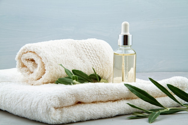 Spa and wellness composition with serum, towels and beauty products.