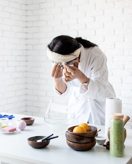 Spa and wellness concept. self care. portrait of a woman in white bath robes making facial mask doing spa procedures